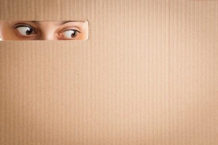 peephole: surprised woman eyes looking through the hole in cardboard