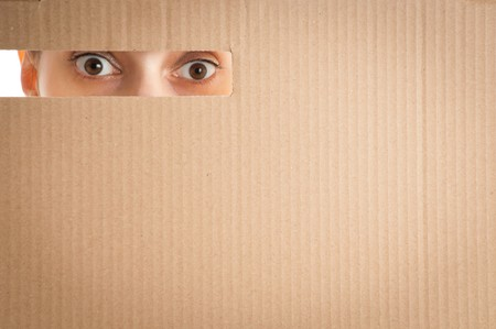 surprised woman eyes looking through the hole in cardboard photo