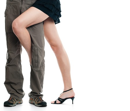 male legs being assaulted by sexy female legs, both isolated on white background photo