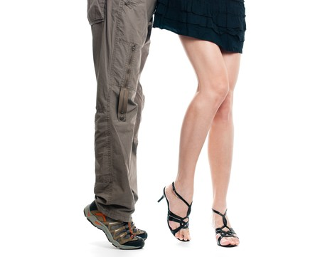 male and sexy female lower body parts isolated on white background. Man on his tiptoes trying to kiss girl photo