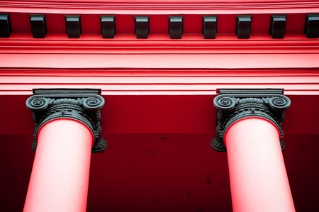 details of two beautiful red columns supporting roof of old red building photo