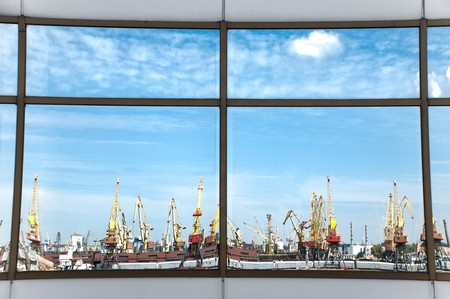 sea port cranes with blue cloudy sky in background reflecting in windows of modern office building photo