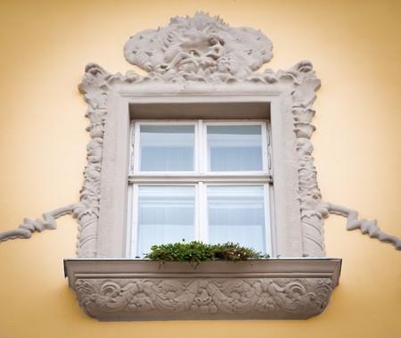 stucco facade: bella vecchia stucchi finestra con fiore di lavoro sulla facciata della vecchia casa in Europa