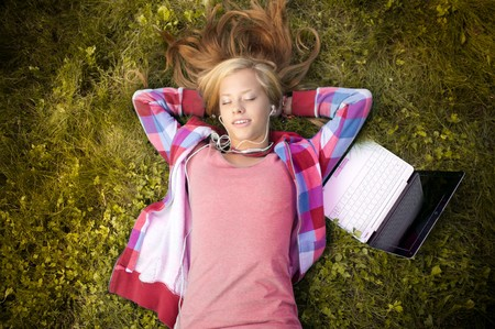 beautiful young student girl with laptop lying on grass in park, smiling with her eyes closed and listening to music photo