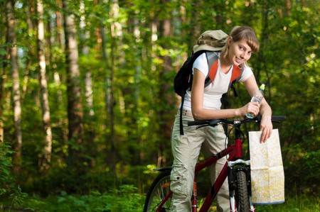 beautiful young woman sitting on her bicycle with bottle of water in hand and map in the middle of summer forest photo