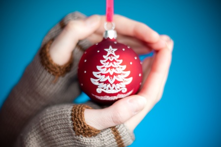 young womans hands against blue background wearing winter clothes holding red christmas ball toy photo