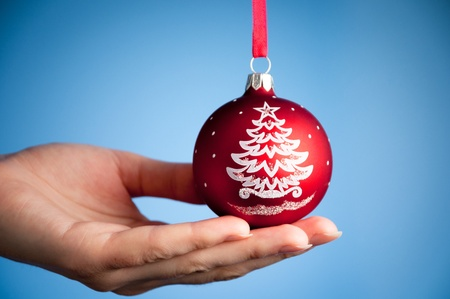 hand of the young woman against blue background holding red christmas ball toy photo