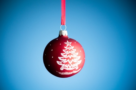 red christmas toy ball hanging on the red ribbon against blue background Stock Photo - 9007210