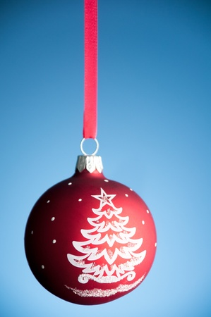 red christmas toy ball hanging on the red ribbon against blue background Stock Photo - 9007198