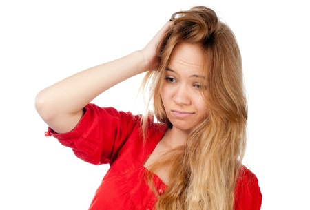beautiful confused teenage girl with hand in her hair, looking away from camera, isolated on white background photo