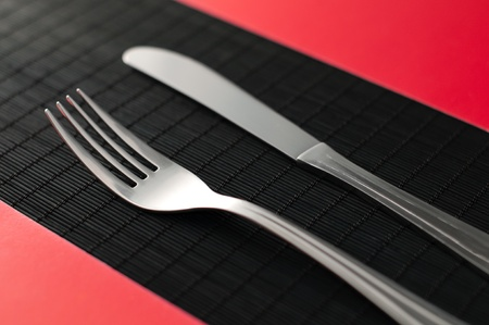 knife and fork on the on black table red napkins by the sides of the flatware photo