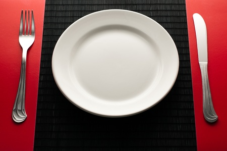 dinner plate: empty white plate on black table with knife and fork on red napkin by the sides of the plate