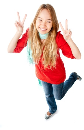 beautiful smiling teenage girl making victory sign with both of her hands, smiling and looking into the camera with her eyes almost closed. Isolated on white background photo