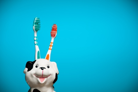 two toothbrushes in the glass resembling smiling dalmatian dogs head against blue background photo