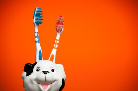 two toothbrushes in the glass resembling smiling dalmatian dogs head against orange background photo