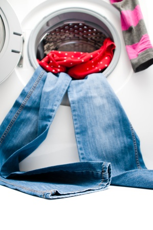 Blue jeans and red shirt hanging out from the door of the washing machine. Space for copy on the floor. Focus is on the lower part of the jeans. Isolated on white background. photo