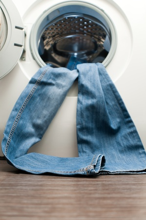 white wash: Blue jeans hanging out of the door of the washing machine. Space for copy on the floor. Focus is on the lower part of the jeans.
