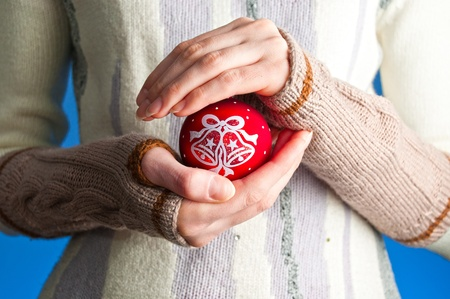 young woman against blue background wearing winter clothes holding red christmas ball toy in her hands photo