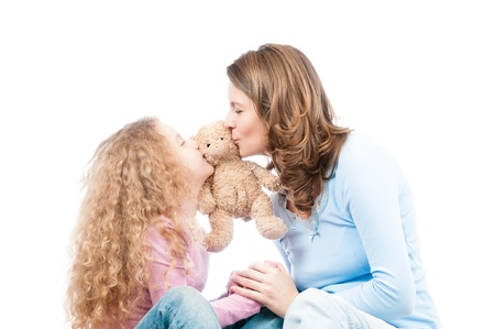 Happy and beautiful young mother and little daughter kissing teddy bear toy. Isolated on white background. photo