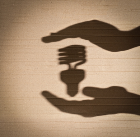 shadow of human hands holding shadow of fluorescent light bulb against cardboard background photo