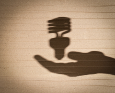 shadow of human hand holding shadow of fluorescent light bulb against cardboard background photo