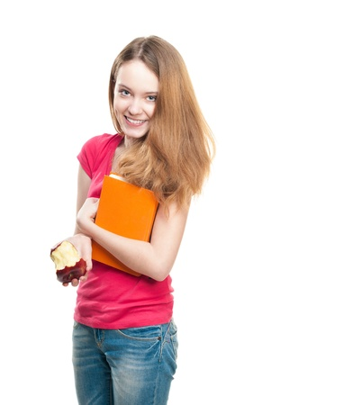 Beautiful and happy young student girl eating red apple and holding book in her hands. Stock Photo - 15183309