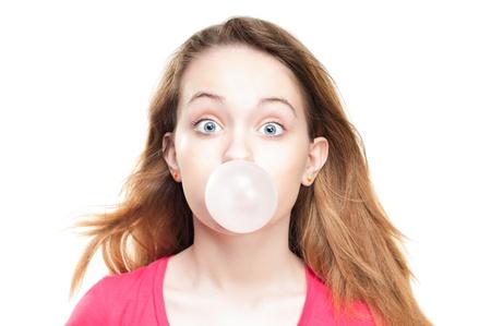 goma de mascar: Chica joven estudiante hermosa y sorprendida o sorprendido soplando burbujas de la goma de mascar. Foto de archivo