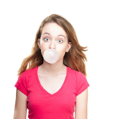 gums: Beautiful and shocked or surprised young student girl blowing bubble from chewing gum. Looking into the camera. Isolated on white background.