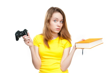 Beautiful and thoughtful young student girl with book in one hand and video game controller in the other. Stock Photo - 14821911