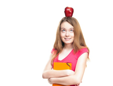 Beautiful and happy young student girl with apple on her head and book in her hands. Stock Photo - 14821765