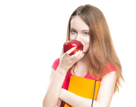 Beautiful and happy young student girl eating red apple and holding book in her hands. Stock Photo - 14848242