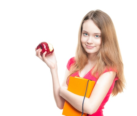 Beautiful and happy young student girl eating red apple and holding book in her hands. Stock Photo - 14821959