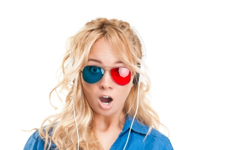 Beautiful and shocked teenage girl watching 3d movie. Wearing 3d glasses and headphones.  photo