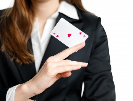 ace: Young businesswoman holding ace of hearts in her hand before her, isolated on white background.