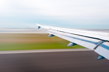 plane landing: View of air plane wing during take off or landing. Motion blur of airport grounds and sky.