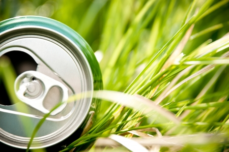 opened green aluminum can (bottle) laying in green grass photo
