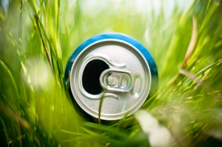 opened blue aluminum can (bottle) laying in green grass, very shallow depth of field