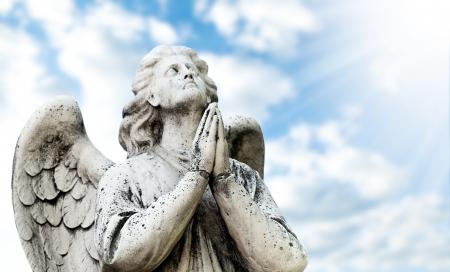 ange gardien: Belle statue de l'ange priant, le ciel bleu avec des nuages ??et soleil avec des rayons en arrière-plan Banque d'images