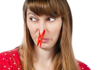 nariz: Joven y bella mujer con pinza roja en su nariz. Aislado sobre fondo blanco