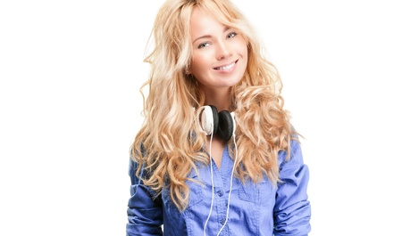 Beautiful and happy teenage girl with headphones. Smiling and looking into the camera. Isolated on white background. photo