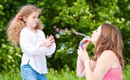 mother blowing soap bubbles at her displeased daughter photo
