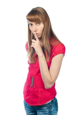 Beautiful young woman looking into the camera and calling to silence with gesture of hand: finger at her lips. Stock Photo - 14848711