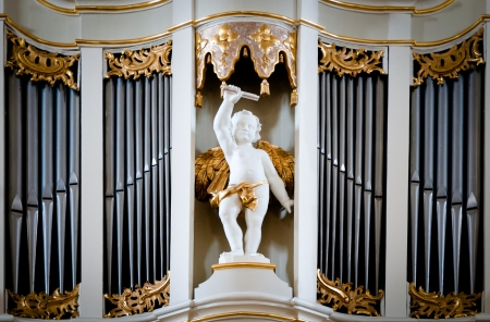 Statue of angel at old organ inside Vilnius cathedral, Lithuania, Europe. Sculpture of small angel boy with wings with metal pipes of organ in background.