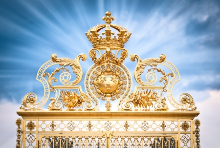 corona real: Puerta de oro adornado de Chateau de Versailles con el cielo azul, con nubes de fondo. Los rayos de luz de la puerta. París, Francia, Europa.
