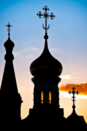 Beautiful silhouette of russian church domes against cloudy sunset sky photo
