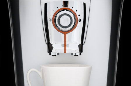 close up front view of modern automatic espresso coffee machine. White cup under nozzle, black background photo