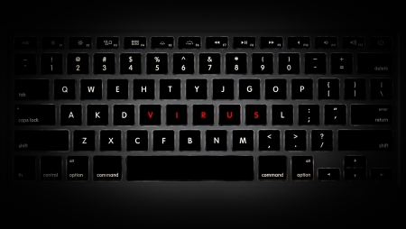 computer hacker: Dark image of computer keyboard with keys rearranged to make up word virus.