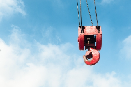 red old crane hook with blue cloudy sky in background. photo