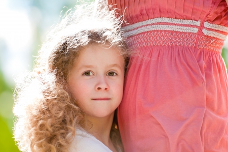 beautiful little and happy daughter hugging her mother and looking into the camera. Nature background. photo