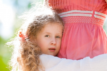beautiful little daughter hugging her mother and looking into the camera. Nature background. photo